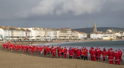 In Pictures: Pudding pursuit sees Santas take to the beach